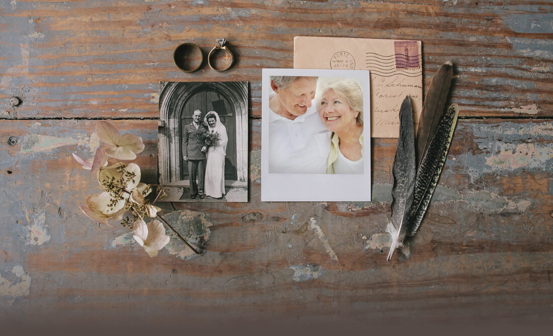 A photo collage with one polaroid photo of elderly couple, postmarked letter, old wedding photo, 2 rings, a flower and feathers for decoration